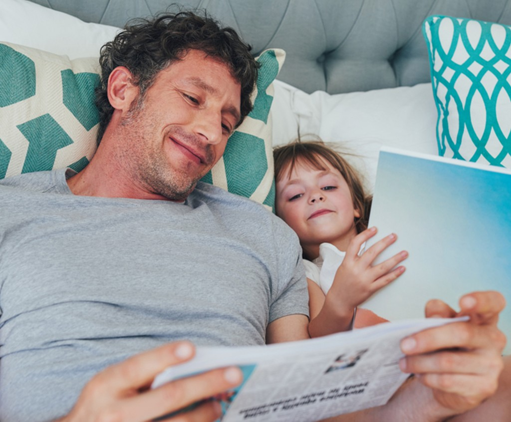 a happy father and daughter resting in a bed while reading books